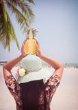 时尚美丽的妇女画象后方用新鲜的菠萝阻止-假期在热带海滩在夏天 免版税库存照片