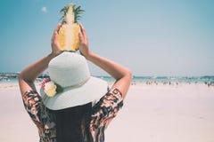 时尚美丽的妇女画象后方用新鲜的菠萝阻止-假期在热带海滩在夏天 免版税图库摄影