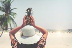 时尚美丽的妇女画象后方用新鲜的菠萝阻止-假期在热带海滩在夏天 库存图片