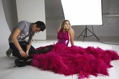 时尚美发师在演播室调整模型的鞋类 免版税库存照片