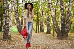 时尚蓝色牛仔裤和红色袋子的少妇走在秋天的 免版税库存照片