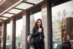 时尚街道一个美丽的女孩的样式画象的关闭偶然成套装备的在城市走 美丽的浅黑肤色的男人保留咖啡 图库摄影