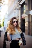 时尚街道一个美丽的女孩的样式画象的关闭偶然成套装备的在城市走 免版税库存照片