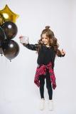 时尚衣裳和baloons的小现代行家女孩,由她的手得到和平 Selfie 拍在电话的照片 免版税库存图片