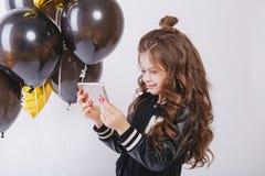 时尚衣裳和baloons的, Selfie小现代行家女孩 拍在电话的照片 免版税库存图片