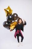 时尚衣裳的小现代行家女孩拿着baloons并且由她的手得到和平 免版税库存照片