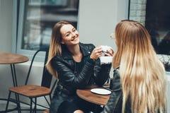 时尚衣裳的谈话两个美丽的少妇有休息和饮用的咖啡在室外的餐馆 免版税库存图片
