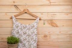 时尚趋向-在花卉图案的礼服在挂衣架和耳环垂悬在木背景 库存图片