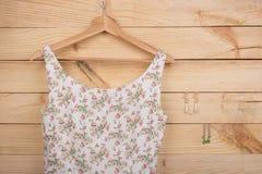 时尚趋向-在花卉图案的礼服在挂衣架和耳环垂悬在木背景 免版税图库摄影
