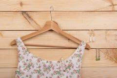 时尚趋向-在花卉图案的礼服在挂衣架和耳环垂悬在木背景 免版税库存图片