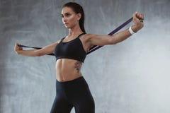 时尚运动服的体育妇女行使与橡皮筋的 免版税库存图片