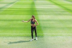 时尚运动服的健身运动的女孩和节律唱诵的音乐在橄榄球场,户外运动跳舞 获得愉快的性感的妇女乐趣  免版税图库摄影