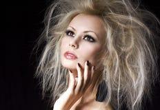 时尚金发碧眼的女人女孩。有专业构成和湿气发型的美丽的白肤金发的妇女,在黑色。时髦模型 免版税库存图片