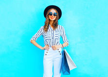 时尚年轻微笑的妇女佩带购物袋,黑帽会议,在摆在城市的五颜六色的蓝色背景的白色裤子 图库摄影
