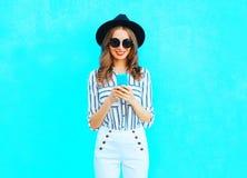 时尚年轻微笑的妇女在城市使用佩带在五颜六色的蓝色背景的一个智能手机一台黑帽会议和提包传动器 库存照片