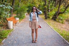 时尚年轻美丽的女孩在公园走  图库摄影