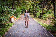时尚年轻美丽的女孩在公园走  免版税库存图片