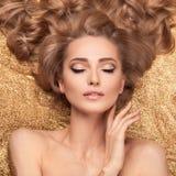 时尚说谎在金黄闪烁的秀丽女孩 免版税库存照片