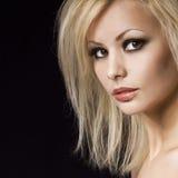 时尚画象。有专业构成和发型的美丽的白肤金发的妇女,在黑色。时髦样式模型 免版税库存图片