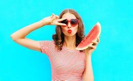 时尚画象妇女拿着切片西瓜和吹的嘴唇 免版税库存照片