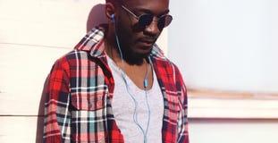 时尚画象年轻非洲人听到在耳机的音乐 库存照片