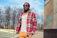 时尚年轻非洲人听到在户外佩带格子花呢披肩红色衬衣和太阳镜街道的耳机的音乐 库存照片