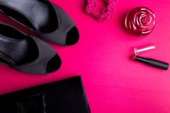 时尚Accessories Set夫人的 黑色粉红色 最小 黑鞋子、镯子、香水、唇膏和袋子在桃红色背景 平的l 图库摄影