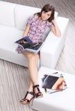 时装杂志读取沙发妇女 库存照片