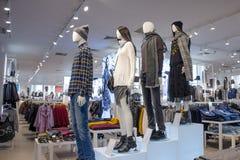时装模特以男人和妇女的形式是在不同的水平上的立场服装店的内部  免版税库存照片