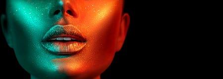时装模特儿在明亮的闪闪发光,五颜六色的霓虹灯,美丽的性感女孩嘴唇的妇女面孔 时髦发光的金皮肤构成 免版税库存照片