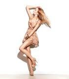 时装模特儿女孩在短的薄绸的米黄礼服穿戴了 库存图片