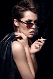 时装模特儿抽烟的香烟佩带的太阳镜 在黑暗的背景的性感的妇女画象 有吸引力时尚女孩摆在 免版税库存图片