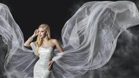时装模特儿礼服,妇女流动的布料翼,飞行的女孩 免版税图库摄影