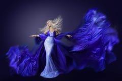 时装模特儿秀丽,飞行在风,振翼的布料的礼服织品 免版税库存照片