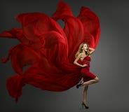 时装模特儿红色礼服,在飞行织品褂子的妇女跳舞 图库摄影
