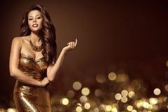 时装模特儿金礼服,金黄褂子的典雅的少妇 免版税库存图片