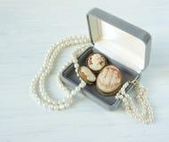 时装模特儿首饰 葡萄酒首饰背景 美丽的珍珠项链、镯子和老有浮雕的贝壳在一个礼物盒在白色木头 平面 库存图片