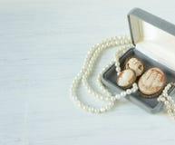 时装模特儿首饰 葡萄酒首饰背景 美丽的珍珠项链、镯子和老有浮雕的贝壳在一个礼物盒在白色木头 平面 免版税库存照片