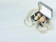 时装模特儿首饰 葡萄酒首饰背景 美丽的珍珠项链、镯子和老有浮雕的贝壳在一个礼物盒在白色木头 平面 免版税图库摄影