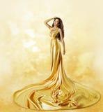 时装模特儿黄色礼服,摆在扭转的秀丽褂子的妇女 库存图片