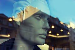 时装模特头在与城市的反射的一个商店窗口里 免版税库存图片