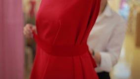 时装设计师在演播室给制造商装饰的钝汉穿衣 时装设计师,裁缝,调整衣裳的裁缝 股票视频