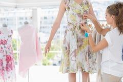 时装设计师测量的模型腰部 免版税库存照片