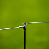 临时金属篱芭和一把标尺和绳索在一个绿色领域 免版税库存照片