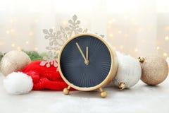 时钟、装饰和圣诞老人帽子在桌上 christmas countdown 免版税库存图片