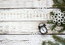 时钟和云杉的分支在白色木背景 免版税库存图片