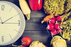 时钟和新鲜蔬菜 夏南瓜,甜椒,红萝卜,圆白菜,花椰菜,萝卜,莴苣,蕃茄 健康d的概念 库存图片