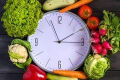 时钟和新鲜蔬菜 夏南瓜,甜椒,红萝卜,圆白菜,花椰菜,萝卜,莴苣,蕃茄 健康d的概念 图库摄影