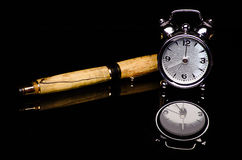 时钟和笔在黑背景 免版税图库摄影