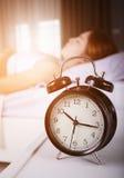 时钟展示上午10点 并且睡觉在与阳光的床上的妇女在平均观测距离 库存图片